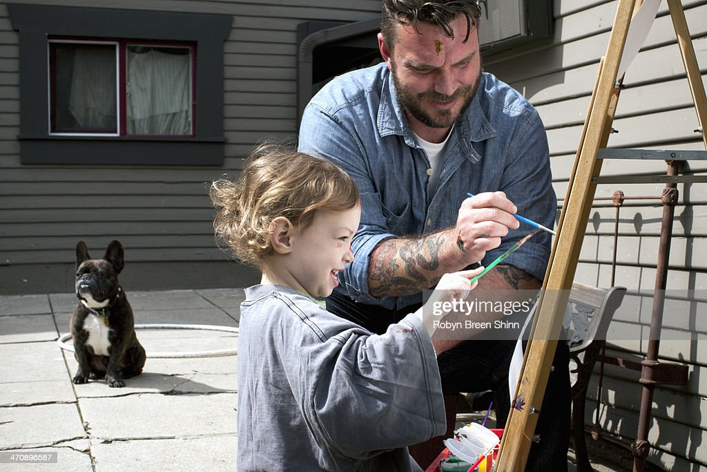 Father and daughter outdoors painting on easel : Stock Photo