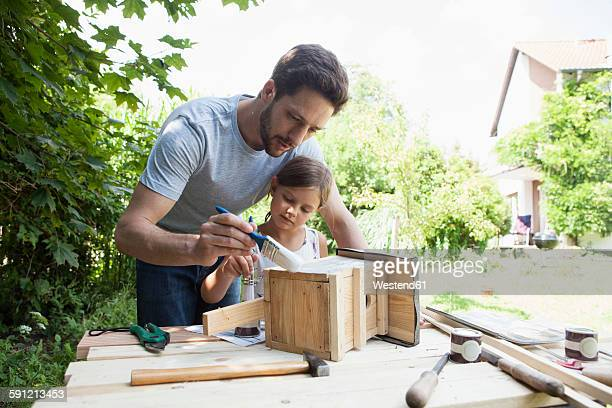 Father and daughter painting a birdhouse