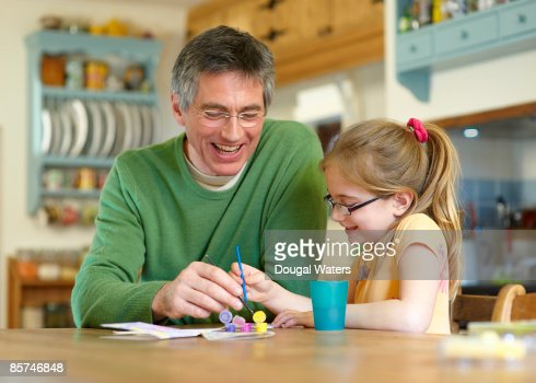 Father and daughter painting together. : Bildbanksbilder