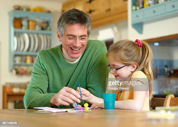 Father and daughter painting together.