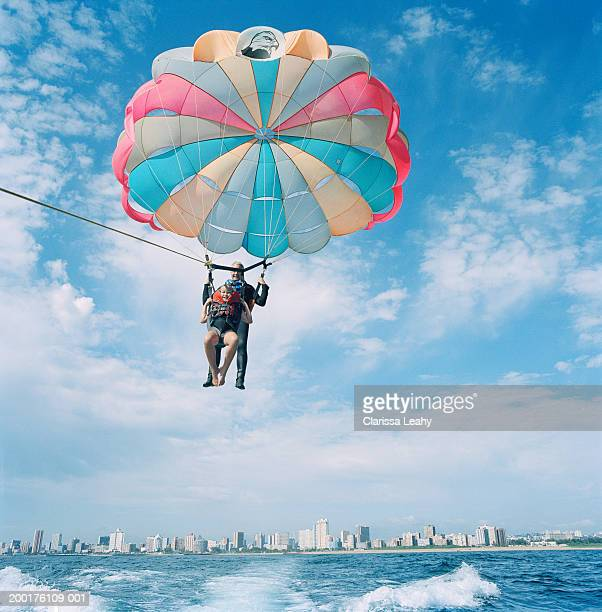 Father and daughter (9-11) parasailing, low angle view