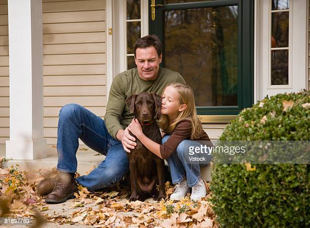 Father and daughter petting dog outdoors