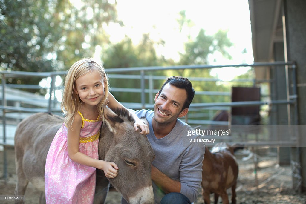 Father and daughter petting donkey : Stock Photo