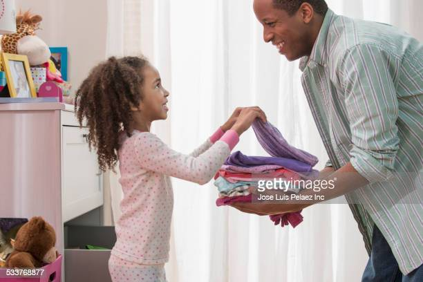 Father and daughter placing laundry in drawers