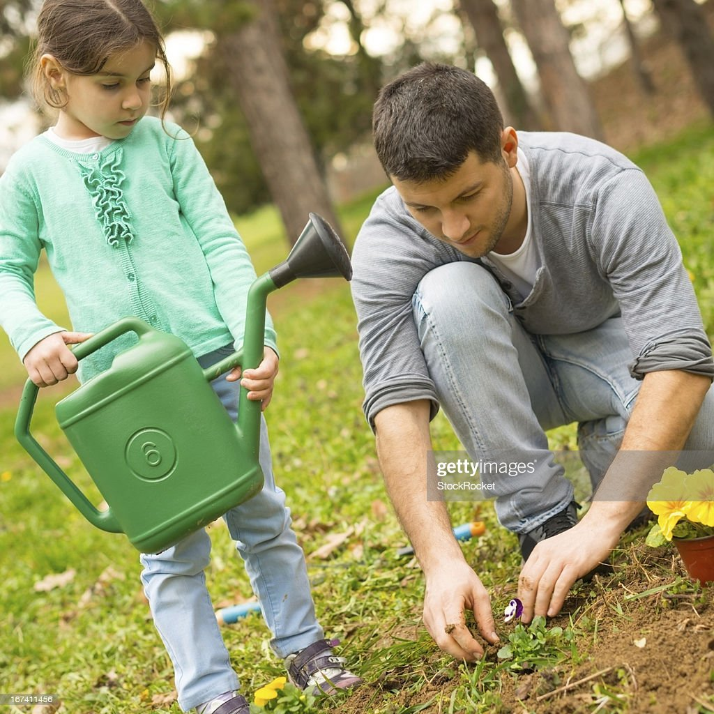 Father and daughter planting flowers : Stockfoto