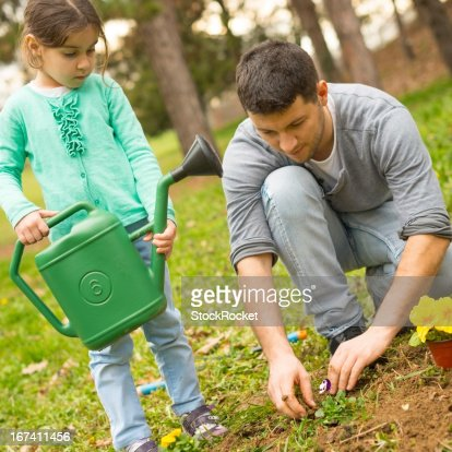 Father and daughter planting flowers : Bildbanksbilder
