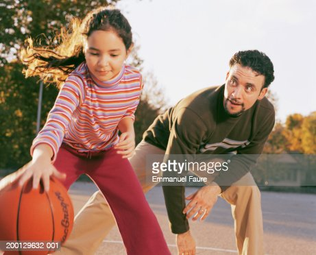 Father and daughter (8-10) playing basketball : Stock Photo