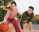 Father and daughter (8-10) playing basketball