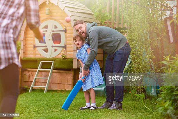 father and daughter playing cricket