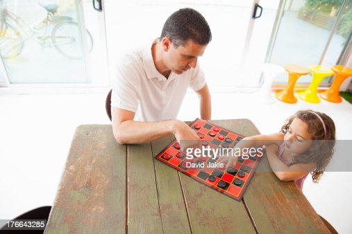 Father and daughter playing draughts
