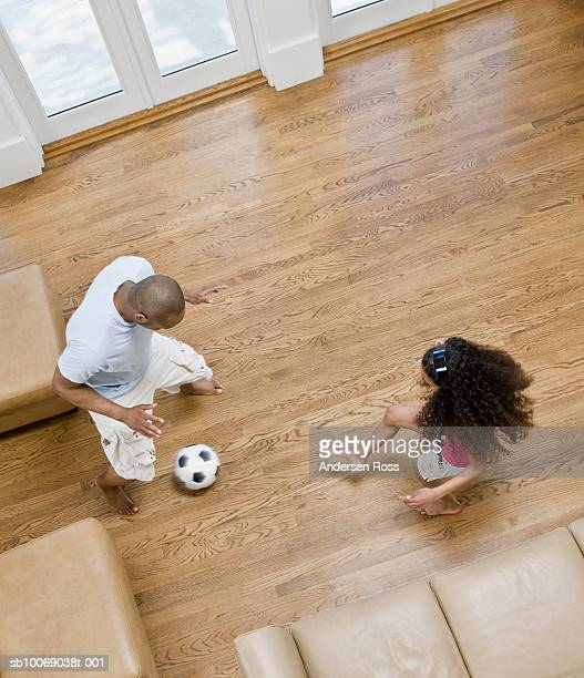 Father and daughter (10-11) playing football, elevated view