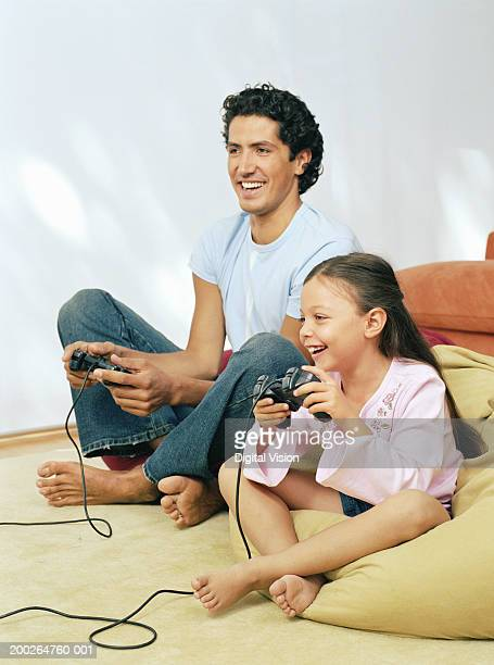 Father and daughter playing games console, smiling