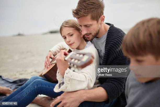 Father and daughter playing guitar on the beach