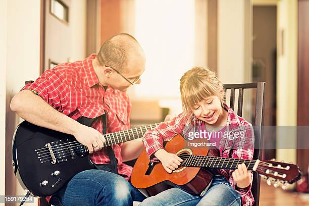 Father and daughter playing guitars together