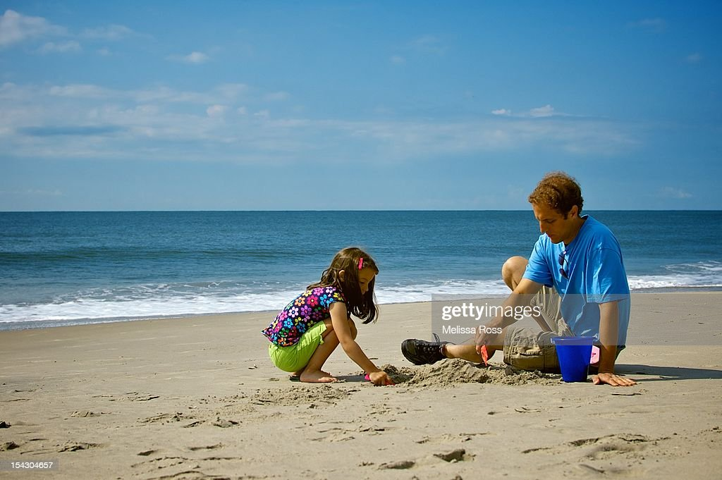 Father and daughter playing in sand at beach