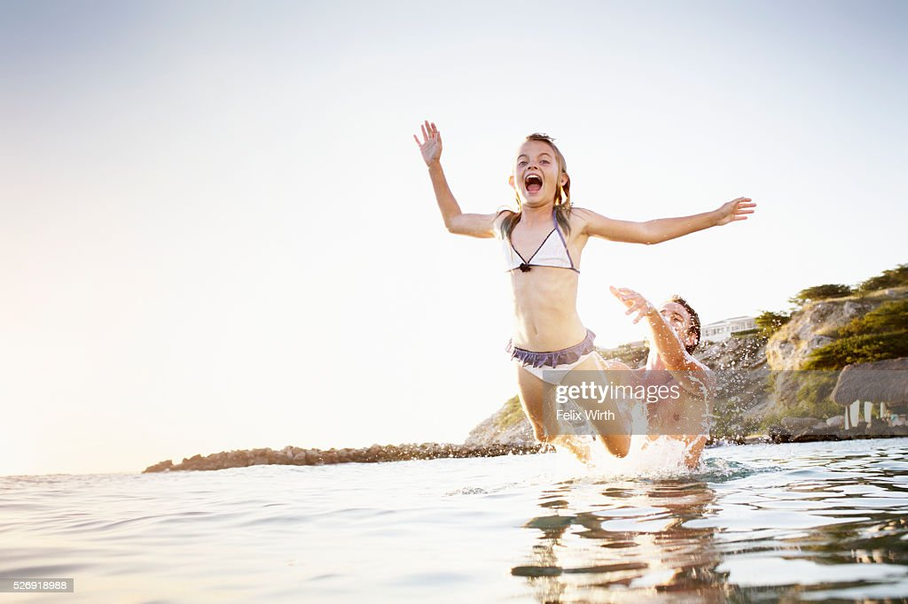 Father and daughter (8-9) playing in sea : Stock Photo