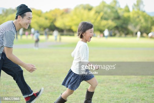 Father and daughter playing in the park : Stock Photo