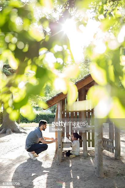 Father and daughter playing in wooden toy house at park during sunny day