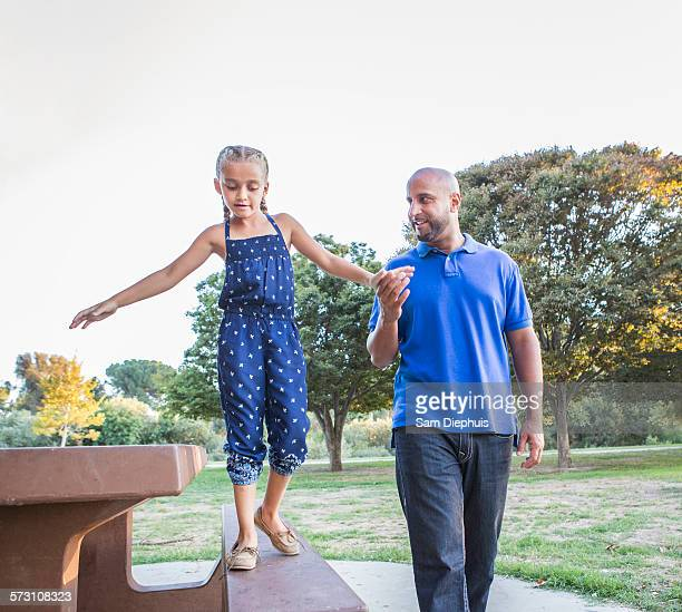Father and daughter playing on picnic table in park