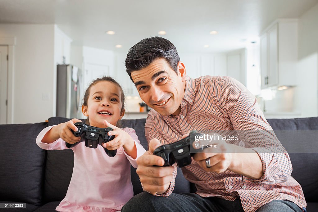 Father and daughter playing video games in living room