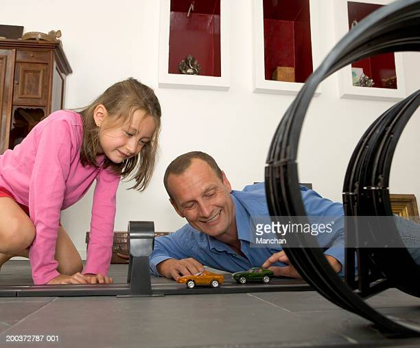Father and daughter (4-6) playing with model car race track