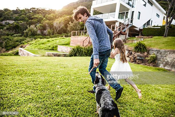 Father and daughter playing with the dog in the backyard
