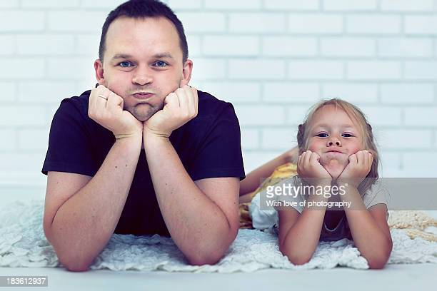 Father and daughter posing with puffed cheeks