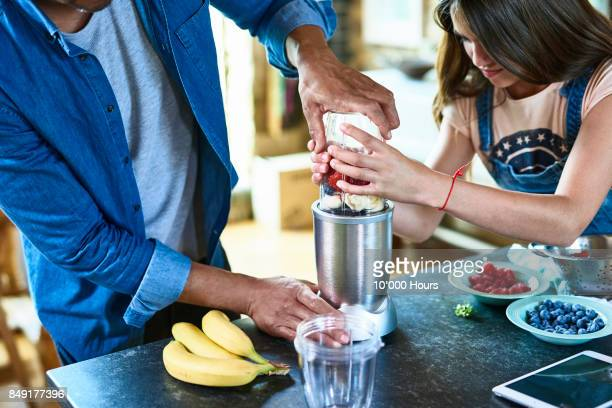 Father and daughter preparing smoothie in kitchen