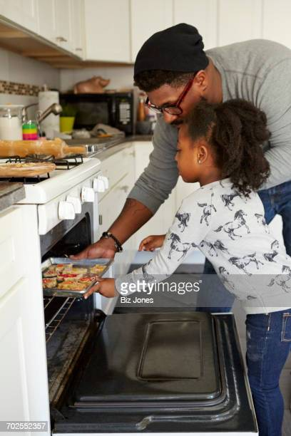 Father and daughter putting unbaked cookies in oven