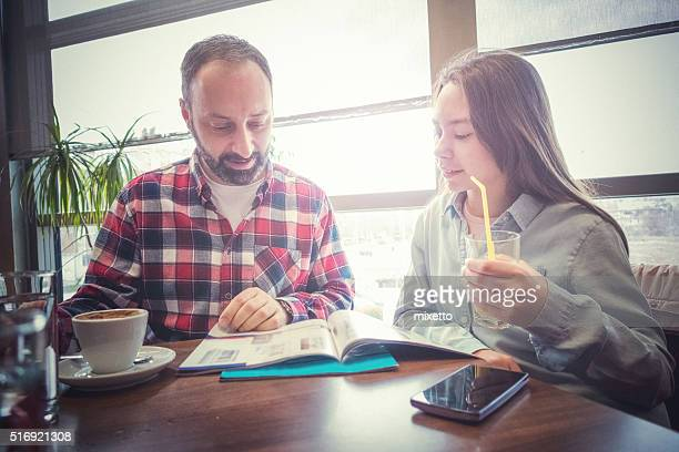 Father and daughter read news magazine