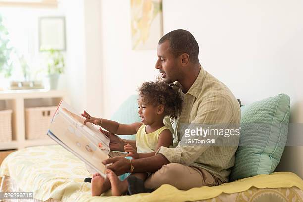 Father and daughter reading book on bed