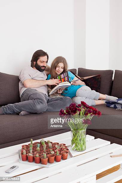 Father and daughter reading book together in living room