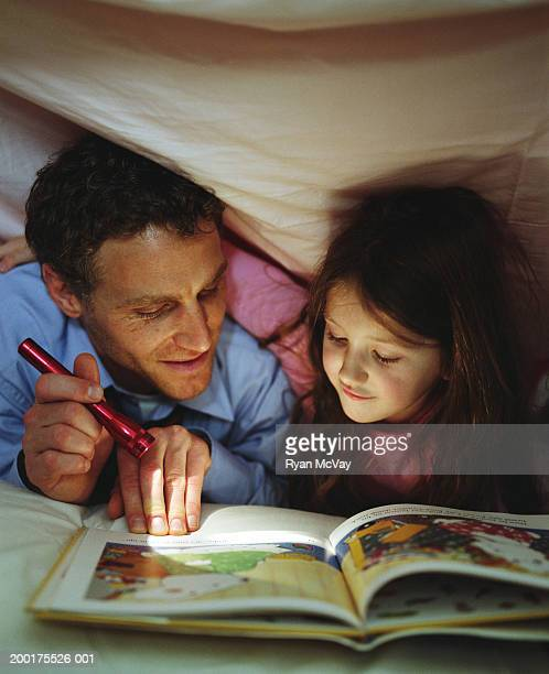 Father and daughter (4-6) reading book under blanket by flashlight