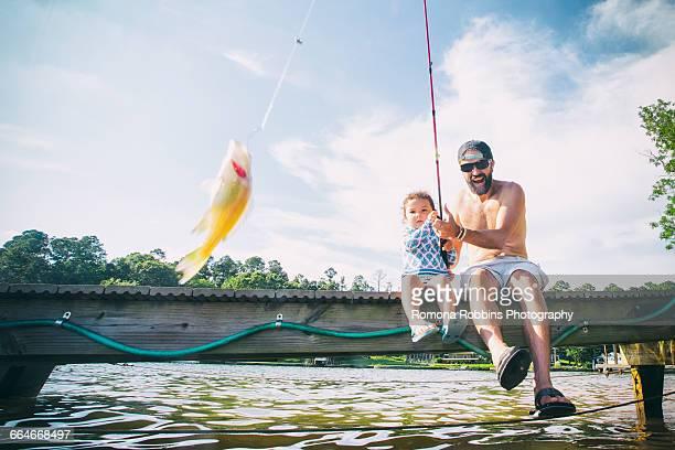 Father and daughter reeling in fish at Lake Jackson, Atlanta, Georgia, USA