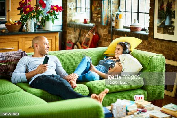 Father and daughter relaxing on sofa