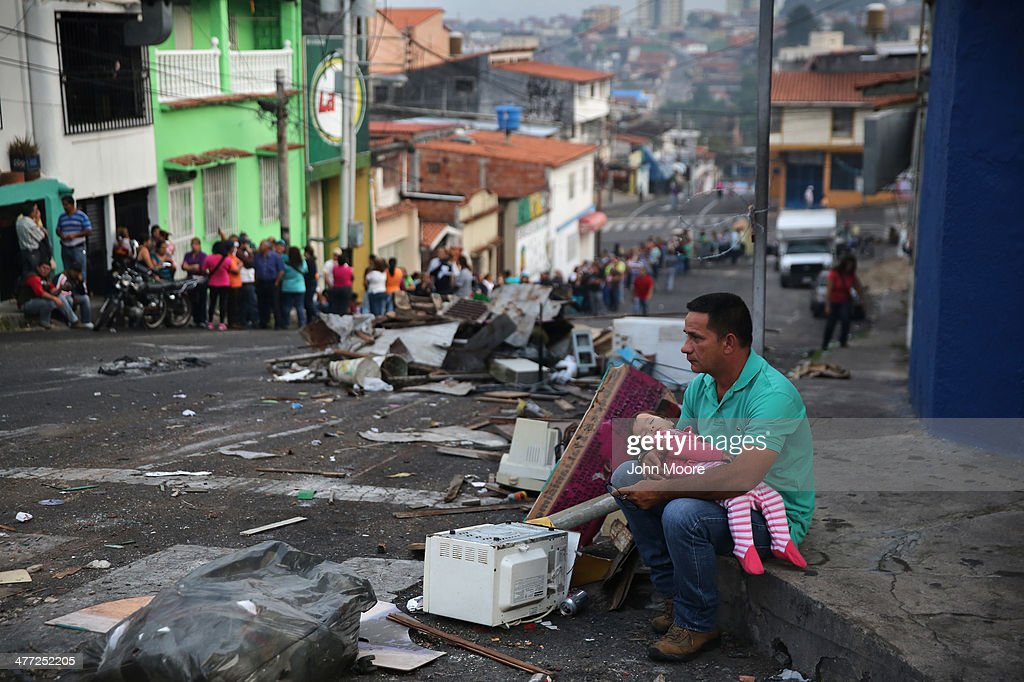 A father and daughter rest while someone holds their place before sunrise in a long line to buy basic foodstuffs at a supermarket on March 8, 2014 in San Cristobal, the capital of Tachira state, Venezuela. Shortage of such products as flour, milk and sugar have made life increasingly difficult for residents of Tachira, which has been a focal point for anti-government protests for almost a month.