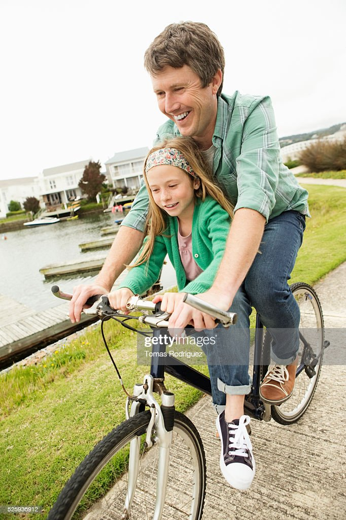 Father and daughter (8-9) riding bicycle : Stockfoto