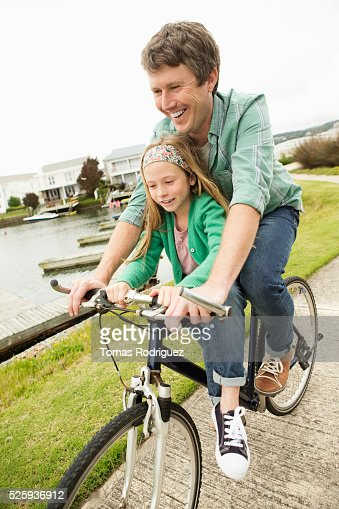 Father and daughter (8-9) riding bicycle : Photo