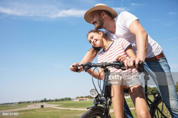 father and daughter riding bicycle