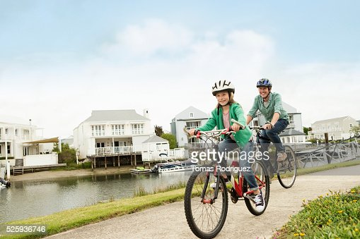 Father and daughter (8-9) riding bicycles : Stockfoto