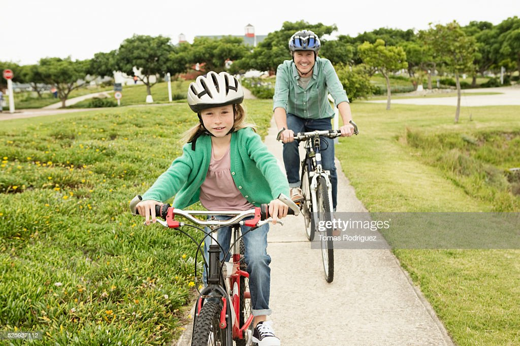 Father and daughter (8-9) riding bicycles : Photo