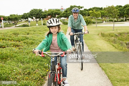 Father and daughter (8-9) riding bicycles : Stock Photo