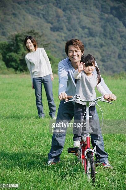 Father and daughter riding bike in meadow