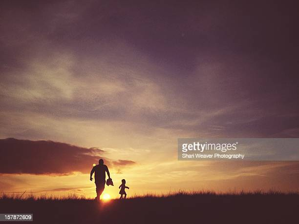 Father and daughter running up hill at sunset