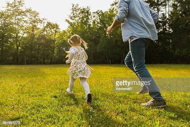 Father and daughter running with paper windmill on meadow