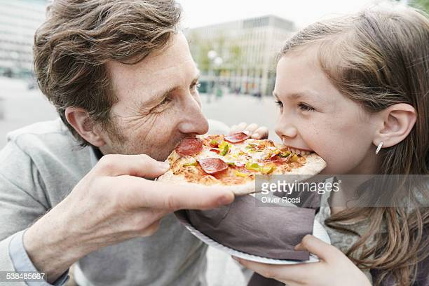 Father and daughter sharing a pizza