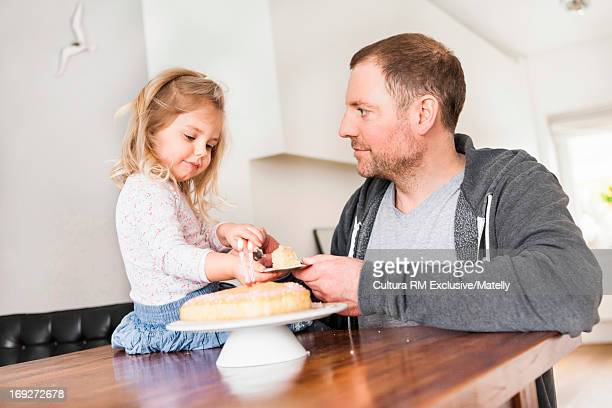 Father and daughter sharing birthday tea