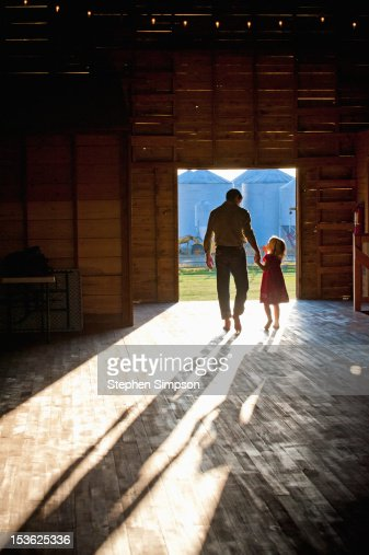 Father And Daughter Silhouette In Barn Doorway Stock Photo