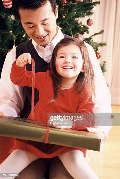 Father and Daughter Sit on the Floor Unwrapping a Christmas Present Together