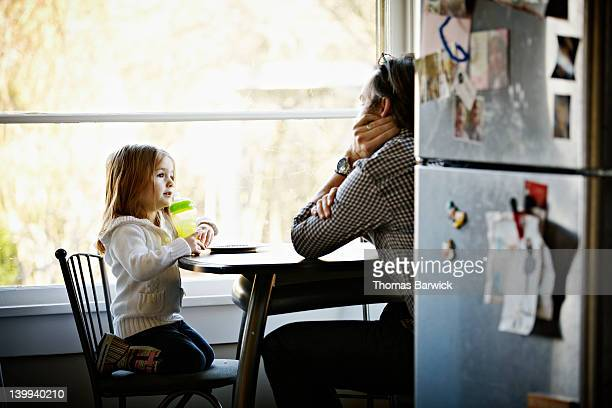 Father and daughter sitting at table in kitchen